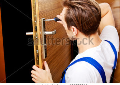 stock-photo-young-man-fixing-the-door-with-screwdriver-404298244
